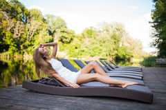Beautiful slim fashionable girl lying in a deck chair near river. Beauty woman Royalty Free Stock Photography