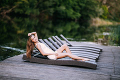 Beautiful slim fashionable girl lying in a deck chair near river. Beauty woman Royalty Free Stock Image