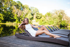 Beautiful slim fashionable girl lying in a deck chair near river. Beauty woman Royalty Free Stock Photos