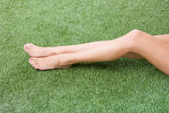 Beautiful slim female feet on green grass Stock Photos