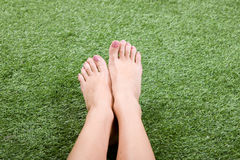 Beautiful slim female feet on green grass Stock Images