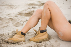 Beautiful, slim female legs in high leather boots. Girl with thick shoes on the sand. Fitness body Royalty Free Stock Image