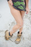 Beautiful, slim female legs in high leather boots. Girl with thick shoes on the sand Royalty Free Stock Photos