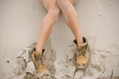 Beautiful, slim female legs in high leather boots. Girl with thick shoes on the sand. Fitness body Stock Photography