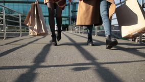Beautiful slim female legs stepping on bridge. Cloesup of sexy elegant female legs in high heels walking on pedestrian bridge at sunset. Two beautiful women stock video footage