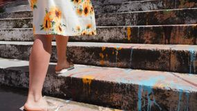 Beautiful slim female legs in summer sandals climbing the stairs. Close Up side view of tanned female legs