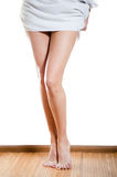 Beautiful slim female legs and towel on hips over white background Stock Photo