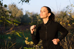 Beautiful slim fitness girl running in nature on sunny spring Royalty Free Stock Image