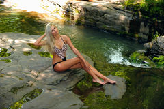Beautiful slim fitness model posing pretty at the mountain river Stock Photos