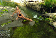 Beautiful slim fitness model posing pretty at the mountain river Stock Photography