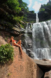 Beautiful slim fitness model posing in front of waterfalls Stock Image