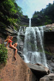 Beautiful slim fitness model posing in front of waterfalls Stock Photo