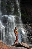 Beautiful slim fitness model posing in front of waterfalls Royalty Free Stock Photography