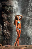 Beautiful slim fitness model posing sexy in front of waterfalls Stock Photos