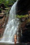 Beautiful slim fitness model posing under waterfalls Royalty Free Stock Image