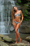 Beautiful slim fitness model posing sexy under waterfalls Stock Photo