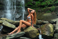 Beautiful slim fitness model posing sexy under waterfalls Stock Photography