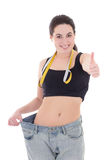Beautiful slim girl in big jeans thumbs up isolated on white Royalty Free Stock Images