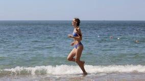 Beautiful slim girl in bikini running along the beach in slow motion stock video footage