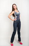 Beautiful slim girl in denim pants and red high-heeled shoes and t-shirt without sleeves.  Royalty Free Stock Image
