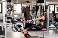Beautiful slim girl dressed in black sport clothes is doing exercises for the abdominals on a special exercise machine royalty free stock photo