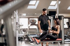 Beautiful slim girl dressed in black sport clothes is doing exercises for the abdominals on a special exercise machine royalty free stock image