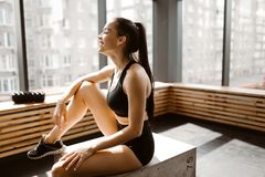 Beautiful slim girl dressed in black sports top and shorts is sitting on a wooden box in the sunlight in front the royalty free stock photos