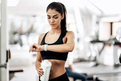 Beautiful slim girl dressed in black sportswear is standing in the gym and looking at her watch royalty free stock image