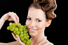 Beautiful slim girl holding a green grapes Royalty Free Stock Image