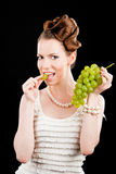 Beautiful slim girl holding a green grapes Royalty Free Stock Images