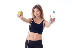 Beautiful slim girl holding out both hands forward shows a fruit Stock Images
