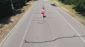 Beautiful slim girl in pink shirt is practicing her run. Young brunette woman in headphones doing exercises in hot summer day at p stock video footage