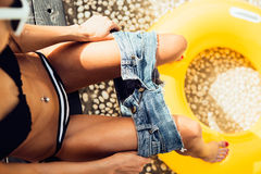 Beautiful slim girl in sexy striped bikini pulls off her shorts. Close up of a sporty young woman in a striped bikini with yellow inflatable swimming ring takes Stock Photography