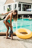 Beautiful slim girl in sexy striped bikini takes off her shorts. Athletic young girl with sporty ass in a striped bikini with yellow inflatable swimming ring Royalty Free Stock Image
