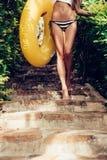 Beautiful slim girl in sexy striped bikini walking down the stai Royalty Free Stock Photos