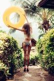 Beautiful slim girl in sexy striped bikini walking down the stai Stock Photos