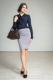 Beautiful , slim girl in a skirt and a handbag. Slim model posing holding a handbag Royalty Free Stock Image