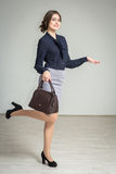 Beautiful , slim girl in a skirt and a handbag. Slim model posing holding a handbag Stock Photography