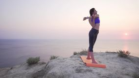 A beautiful and slim girl at sunset doing sports - stretching before outdoor training. 4k stock footage