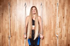 Beautiful slim girl with very long blond hair dressed in a sportswear is standing next to the special rope equipment in stock photography