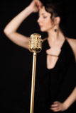 Beautiful slim girl vocalist behind golden vintage microphone. Beautiful emotional young female singer in dress prepare to sing on the stage during live concert royalty free stock photos