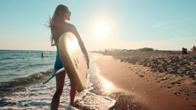 Beautiful slim girl walking on the beach, holding surfboard. Runs in the evening during sunset. Wears a swimming suit