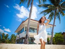 Beautiful slim girl walking on a beautiful tropical beach on the background of a luxury villa. Beautiful slim girl in a white dress on a beautiful tropical beach stock photos
