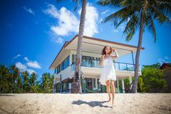 Beautiful slim girl walking on a beautiful tropical beach on the background of a luxury villa. Beautiful slim girl in a white dress on a beautiful tropical beach royalty free stock photos