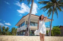 Beautiful slim girl walking on a beautiful tropical beach on the background of a luxury villa. Beautiful slim girl in a white dress on a beautiful tropical beach royalty free stock photo