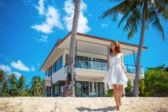 Beautiful slim girl walking on a beautiful tropical beach on the background of a luxury villa. Beautiful slim girl in a white dress on a beautiful tropical beach royalty free stock image