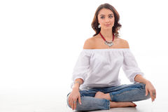 Beautiful slim girl in white dress and blue jeans is posing while sitting. Girl wearing silver jewelry collection, isolated on. White stock photos