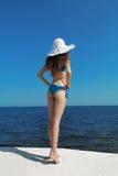 Beautiful slim girl in white hat over blue sky. Enjoyment. Fashi Royalty Free Stock Photo