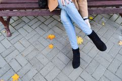 A beautiful slim girl, woman straightens, touches her legs, jeans, pants and boots, shoes sitting on a park bench. The background royalty free stock photos
