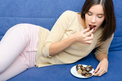Beautiful slim happy young girl eating dessert cookies at home Royalty Free Stock Images